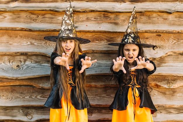 Girls in halloween costumes pretending magic