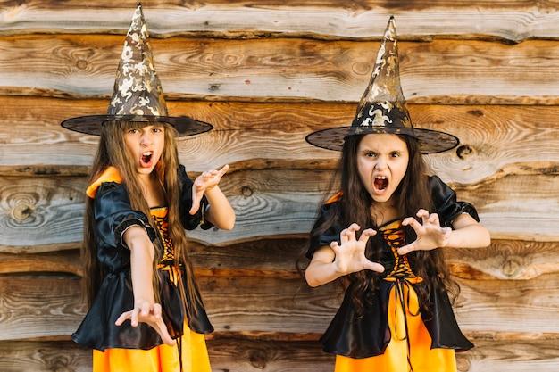 Girls in halloween costumes pretending wicked spell