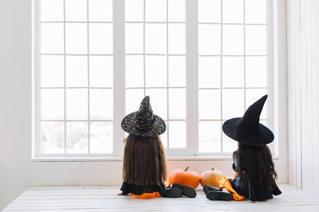 Girls in halloween costumes sitting near window