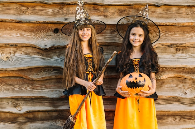 Girls in halloween costumes with broom and pumpkin looking at camera