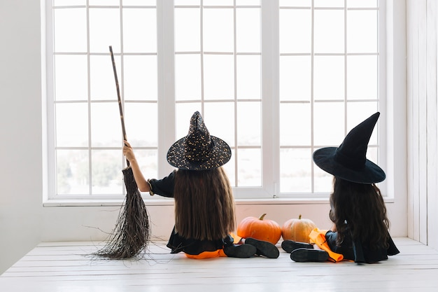 Girls in halloween costumes with broom sitting near window
