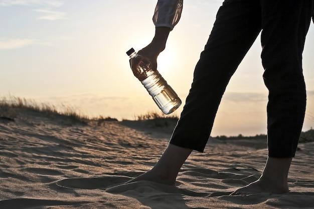 사막에서 물 한 병을 들고 여자 손