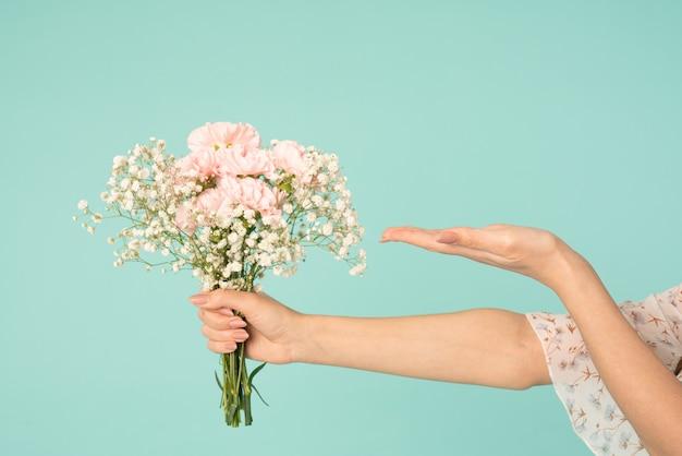 春の花束を持っている女の子の手、開いた手のひらを持つ他の手はあなたの製品を持っています