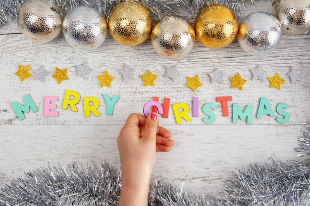 Girls hand placing the letter c into the merry christmas text on the table with baubles and tinsel