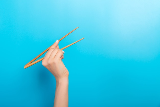 Girls hand showing chopsticks on blue surface
