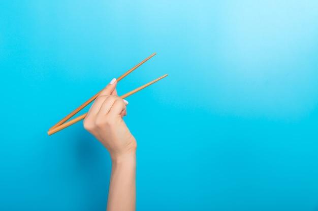 Руки девушки показаны палочки для еды на синей поверхности