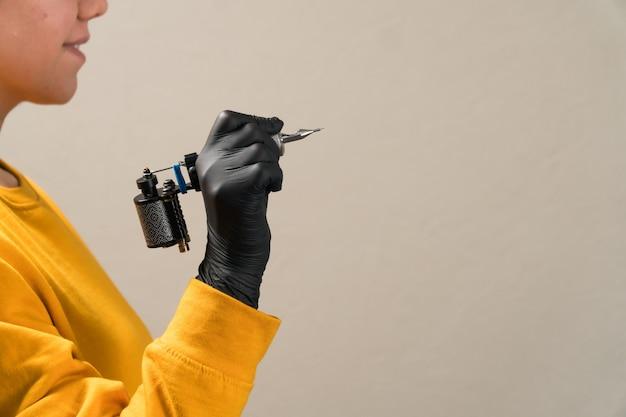 Girls in hands black tattoo machine permanent