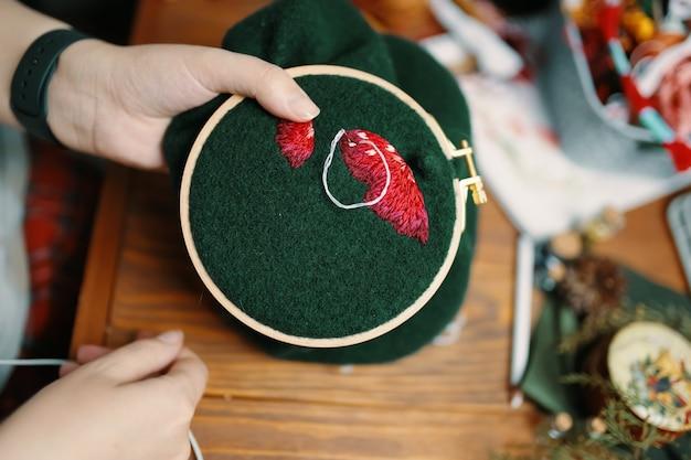 Девушки руки вышивка шляпа мухомора на деревянном столе рамки с разными предметами на фоне кон ...