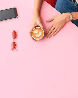 女の子の手はコーヒーカップを持っています。ホームオフィスデスク。ピンクの背景に電話、サングラス、マグカップと女性のワークスペース。フラットレイ、上面図。ファッションブログルック。テキストを追加します。