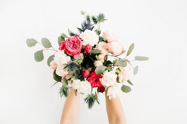 美しい花の花束の大胆なバラ、青いエリンギウム、ユーカリ、白い背景で隔離を保持している女の子の手。フラットレイ、トップビュー