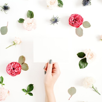 Girls hands holding paper blank on floral frame with red and beige rose flower buds on white background. top view, flat lay
