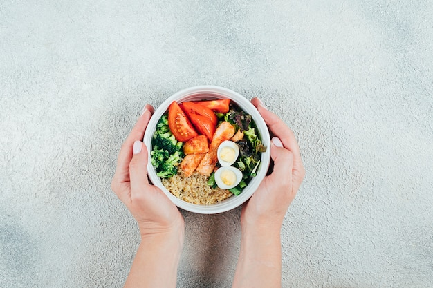 Girls' hands holding salmon poke bowl. fish salad with salmon, couscous, salad mix, vegetables