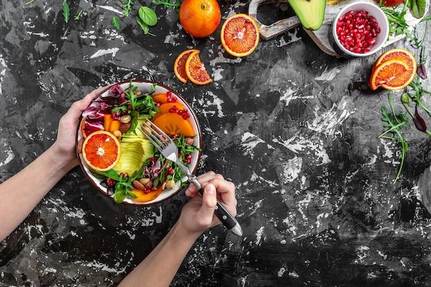 Руки девушки держат вегетарианскую чашу будды с фруктами и овощами на темном фоне, вид сверху.