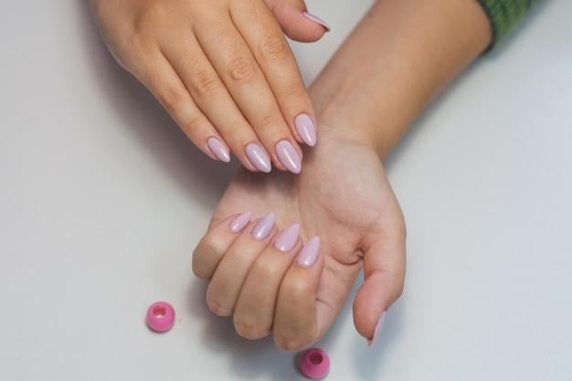 Руки девушки с нежным розовым маникюром на белом фоне