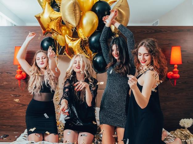 여자들은 즐거운 시간을 보냅니다. 함께 즐거운 시간을 보내십시오. 침대에서 춤을 추는 즐거운 젊은 여성. 처녀 파티. 색종이와 풍선.