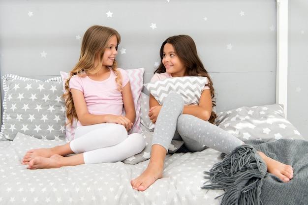 枕の寝坊パーティーでかわいいスタイリッシュなパジャマを着た女の子の幸せな親友や兄弟。お泊まり会を楽しんでいるお姉さんたち。枕投げパジャマパーティー。寝坊パーティーのアイデア。楽しみのための夜の時間。