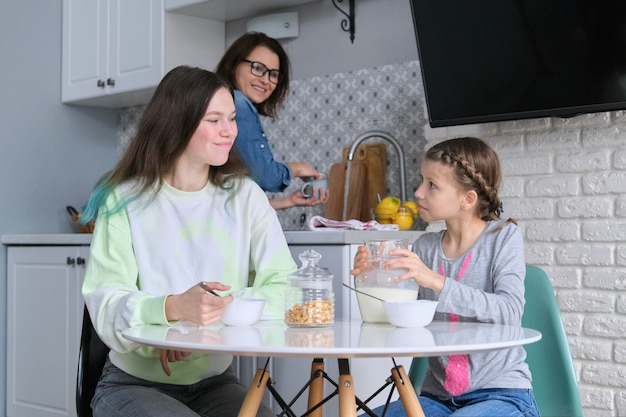 家庭の台所のテーブルに座って朝食をとっている女の子、10代の姉妹と9、10歳の子供が一緒に牛乳とコーンフレークを食べています