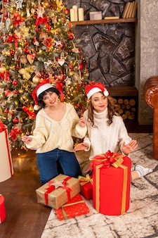 Девочки веселятся и танцуют на рождество в своей гостиной. они улыбаются. на заднем плане украшенная елка и подарки