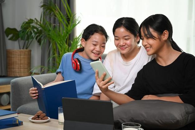Девочки веселятся в выходные, используя смартфон и сидя на диване у себя дома.