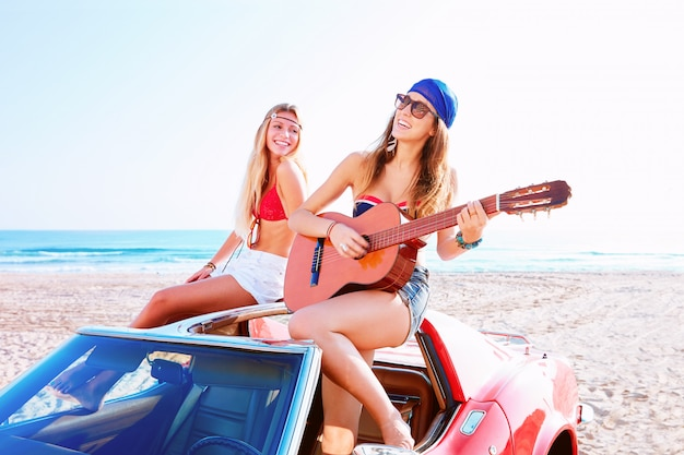 Girls having fun playing guitar on th beach in a car