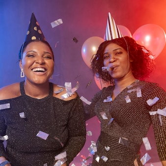 Girls having a good time with party hats and confetti