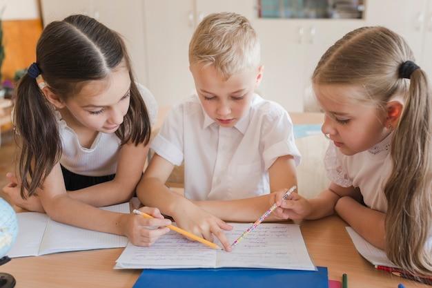 Девушки помогают мальчику с учебой