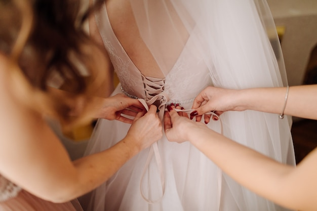 Girls helping bride to put on her dress