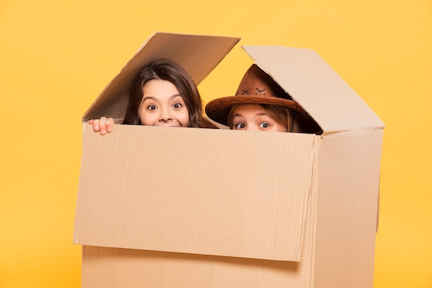 Girls hiding in cartoon box