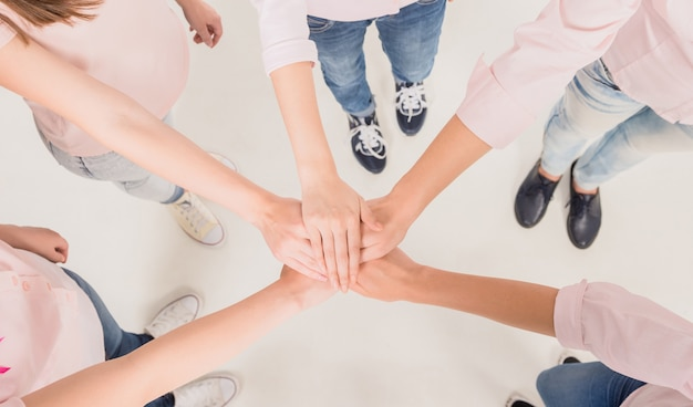 Girls hold hands together and stand in a circle.