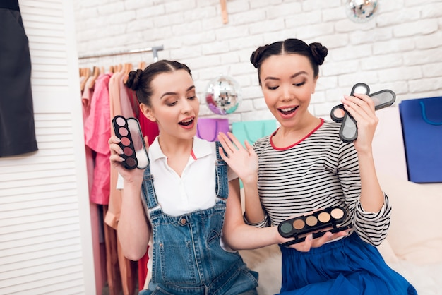 Girls hold up colorful eye shadows to camera