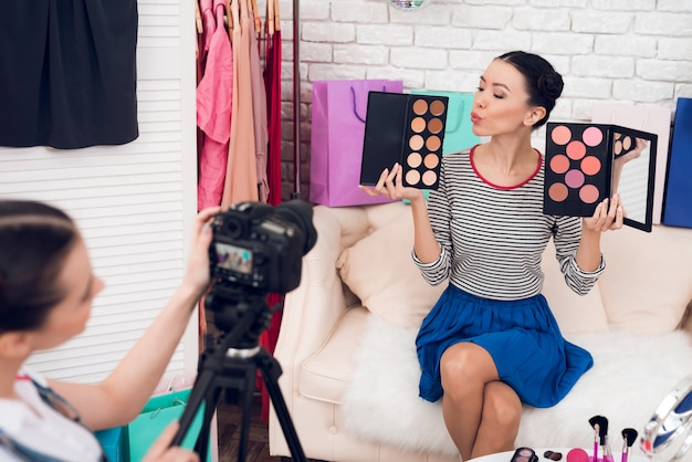 Girls hold up colorful eye shadows with one girl.