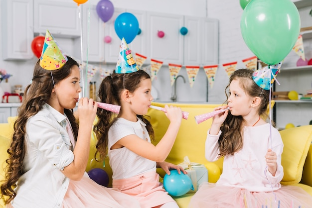 Girls holding balloons and blowing party horn during birthday