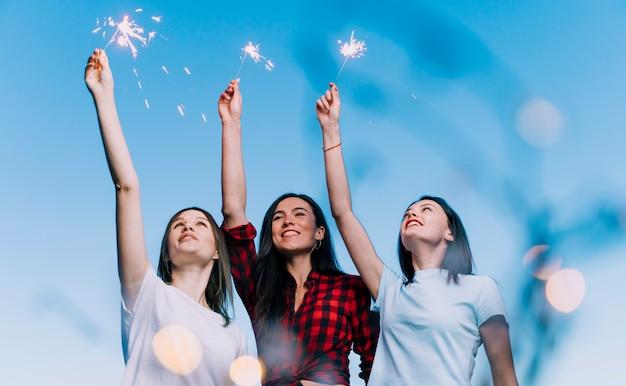 Девушки держат фейерверк на крыше на рассвете