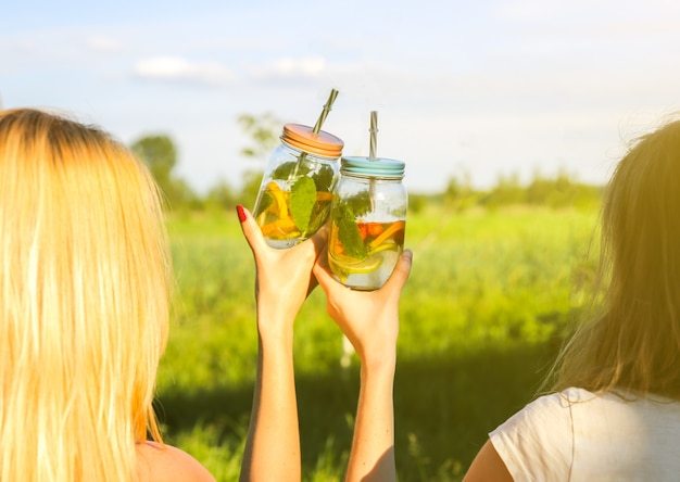 빨대가 든 항아리에 신선한 레모네이드를 들고 있는 소녀들. 음료와 함께 소식통 여름 파티입니다. 건강한 채식주의 생활 방식. 자연에서 친환경. 유리에 민트와 레몬, 오렌지, 딸기.