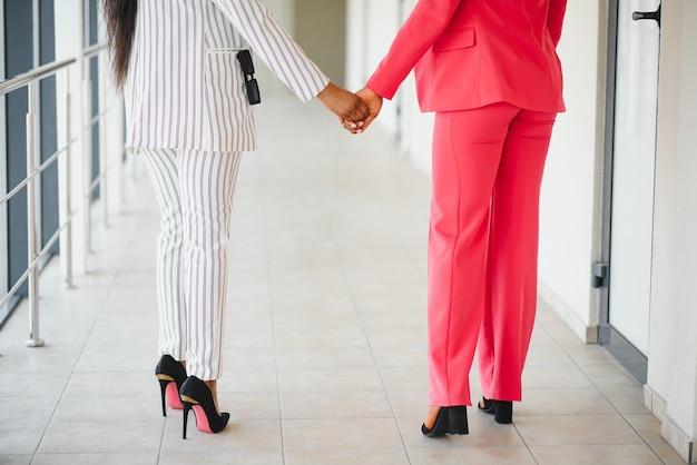 手をつないでいる女の子。手をつないで異なる色の女の子のカップル。 lgbt