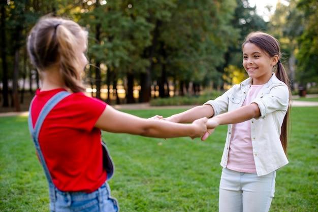 Girls holding hands outdoors