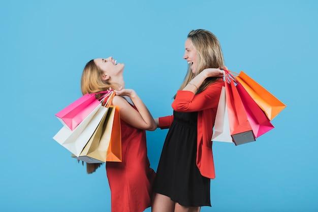 無地の背景に買い物袋を保持している女の子