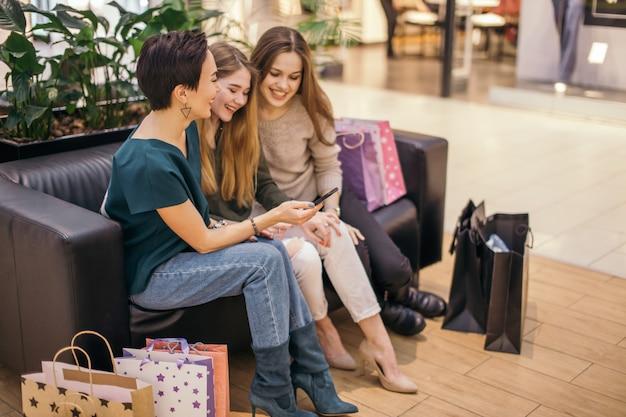 ショッピングバッグを持って、asmart電話を使用し、立っている間笑顔の女の子