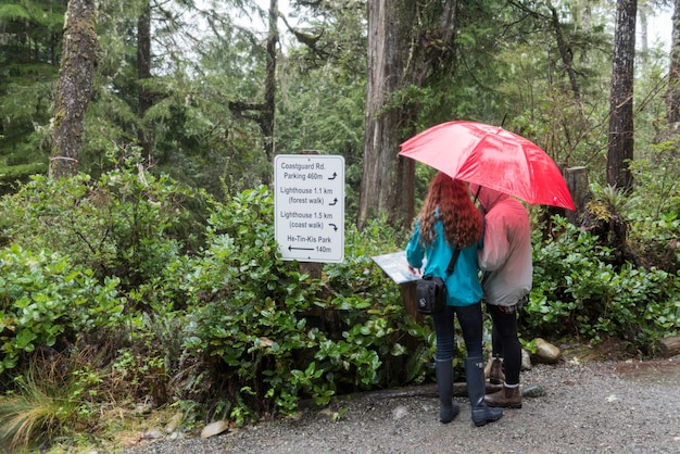 Girls holding an umbrella looking at sign board, pacific rim national park reserve, ucluelet, vancou