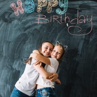 Ragazze che abbracciano vicino alla scrittura di buon compleanno