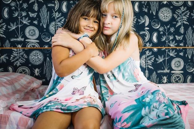 Девушки обнимаются на кровати