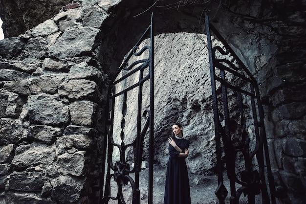 石の開口部に立っている白い襟付きの黒いドレスの女の子