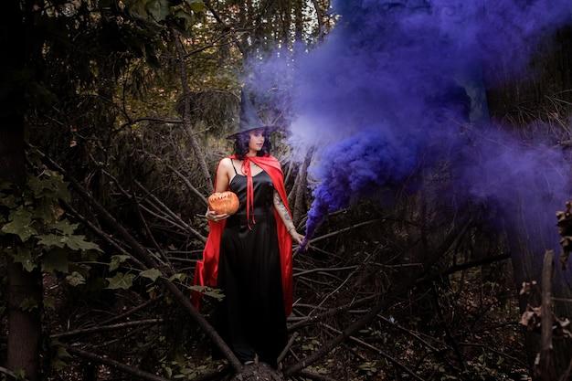 색깔의 연기와 함께 마법의 숲에있는 여자.