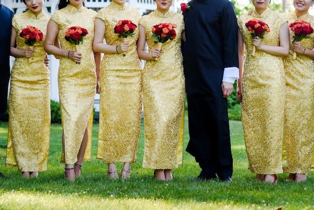 Девушки в китайских платьях с золотым орнаментом стоят вокруг человека в черном