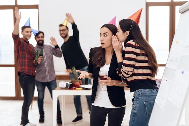 お祝いの帽子をかぶった女の子がオフィスで話しています。