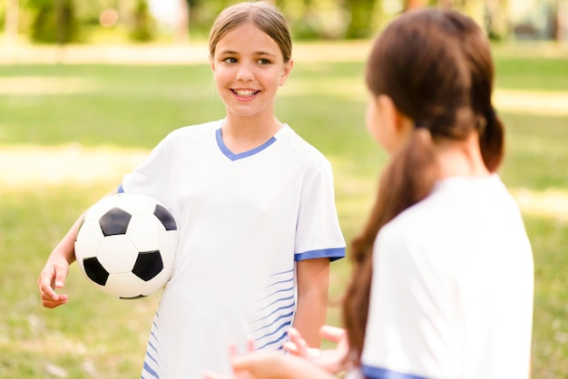 彼らの試合について話しているサッカー用品の女の子