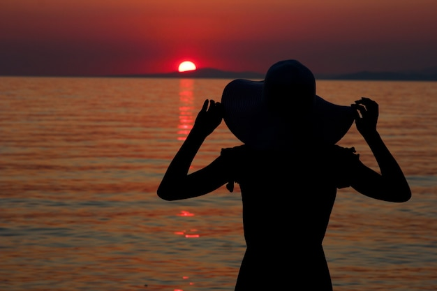 Девушки в шляпе силуэт на берегу моря летом в греции