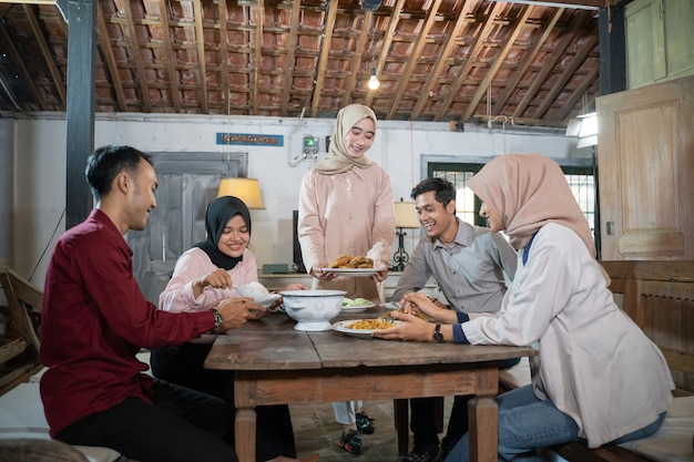 ヒジャーブの女の子と何人かの男性が集まって食堂で一緒に食事をします