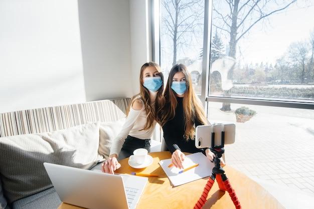 가면을 쓴 소녀들은 사무실에 앉아 블로그를 촬영합니다.