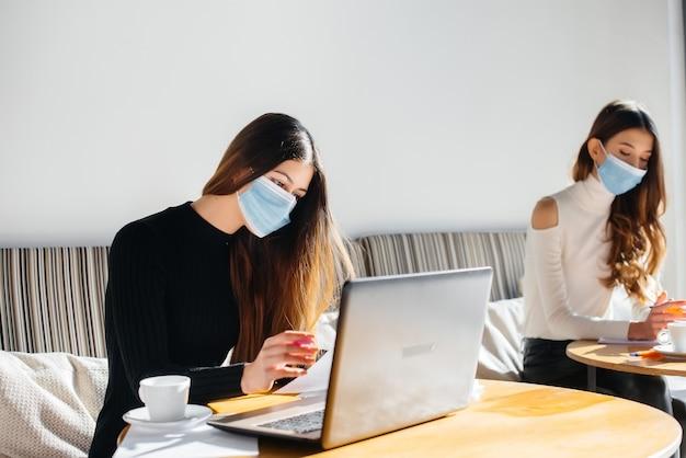 가면을 쓴 소녀들은 사무실에 앉아 노트북에서 일합니다.